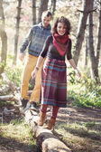 Young woman and man in bright clothes walking along fallen trunk — Stock Photo
