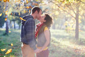 Loving couple kissing in the park in the sunlight on trees backg — Stock Photo