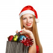 Young woman in santa hat with christmas attributes and gifts — Stok fotoğraf