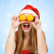 Woman in santa claus hat joking with mandarins — Foto de Stock