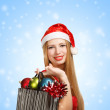 Young woman in santa hat with christmas attributes and gifts — Стоковая фотография