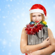 Young woman in santa hat with christmas attributes and gifts — Stock fotografie