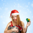 Young woman in santa hat with christmas attributes and little gi — Photo