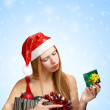 Young woman in santa hat with christmas attributes and little gi — Stock Photo