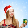 Young woman in santa hat with christmas attributes and little gi — Foto de Stock