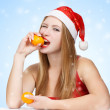 Woman in santa claus hat eating mandarins — 图库照片
