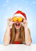 Woman in santa claus hat joking with mandarins — Stock Photo