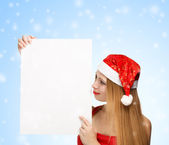 Young woman in santa claus hat with christmas card — Stock Photo