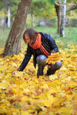 Young woman in the park gathering autumnal leaves — Stock Photo