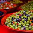 Green and black olives compasition in a red bowl — Stock Photo