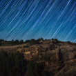 Star trails above rock cliff — Stock Photo