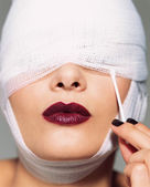 Woman wearing lipstick and bandages — Stockfoto