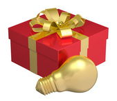 Golden light bulb near red gift box with golden bow — Stock Photo