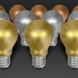Row of golden light bulbs in front of silver and bronze ones on grey textured background — Stock Photo