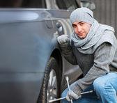 Genç adam bir araba tekerleği değiştirme — Stok fotoğraf