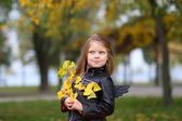 Stylish emotional girl with autumn leaves — Stock Photo