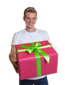 Attractive guy showing his christmas gift — Stockfoto