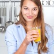 Smiling woman in the kitchen drinking orange juice — Stock Photo