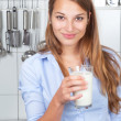 Smiling woman in the kitchen drinking milk — Stock Photo