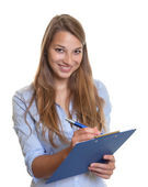 Female secretary writing notes on a clipboard — Stock Photo