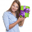 Laughing woman listens on a christmas gift — Stock Photo