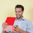 Latin man opening a gift in his living room — Stock Photo #33955857