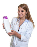 Beautiful laughing female seller presents new lotion — Stock Photo