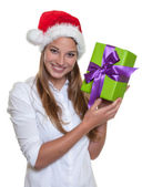 Beautiful woman with christmas hat has a gift in her hand — Stock Photo
