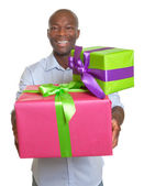 Laughing african man with two gifts for christmas — Stock fotografie