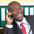 African businessman laughing at phone — Stock Photo
