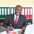 Laughing african businessman writing a message — Stock Photo