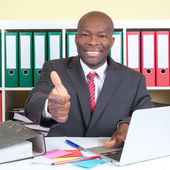 African businessman showing thumb up at his office — Stock Photo