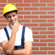 Thinking young worker in front of a brick wall — Stock Photo #35582379