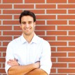 Handsome latin guy in front of a brick wall — 图库照片