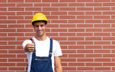 Young worker showing tumb up in front of a brick wall — Stock Photo