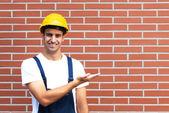 представление молодого работника перед кирпичной стены — Стоковое фото