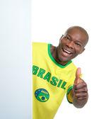 Brazilian soccer fan behind a blank signboard showing thumb — Fotografia Stock