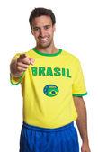 śmiejąc się fan piłki nożnej brazylijski, wskazując na aparat — Zdjęcie stockowe