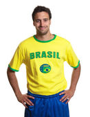 Attractive guy with brazilian jersey smiling at camera — Стоковое фото