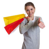 Laughing woman with shopping bags showing thumb up — Stock Photo