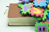 Old book with colorful foam puzzle mat isolated on white background — Stok fotoğraf