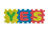Word YES formed with colorful foam puzzle mat isolated on white background — Stockfoto