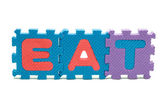 Word EAT formed with colorful foam puzzle mat isolated on white background — 图库照片
