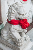 Chinese lion statue with red ribbon — Zdjęcie stockowe