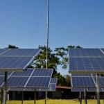 Solar panels and wind turbine against blue sky — Stock Photo #33594145