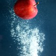 Apple in splash of water — Stock Photo