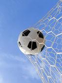 Soccer ball in net on blue sky — Stock Photo