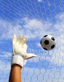 Soccer goalkeeper's hands reaching for the ball, with net and sk — Stock Photo