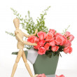 Stock Photo: Wooden puppet happy with pink rose in plastics watering can