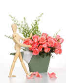 Wooden puppet happy with pink rose in plastics watering can — Stock Photo